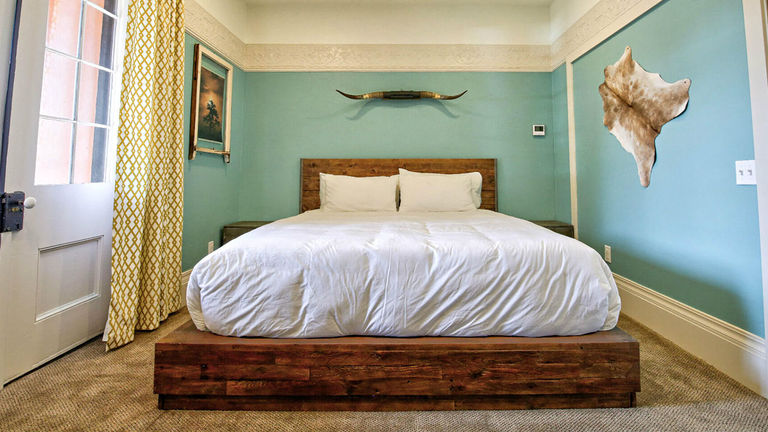 The Adobe Suite features a king bed set in reclaimed wood, an 1849 original French door, an oversize bathroom with a rain shower and direct access to the wraparound porch.