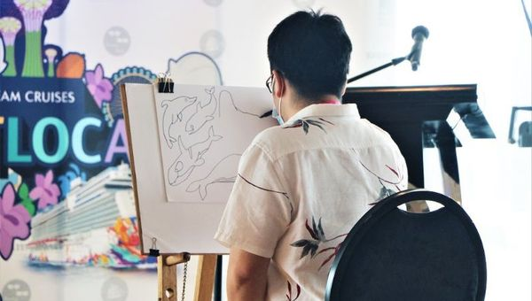 The Animal Project's artist, Tay Jun-Yi, demonstrates how he draws the marine animals printed on the exclusive Dream Cruises denim pouch.