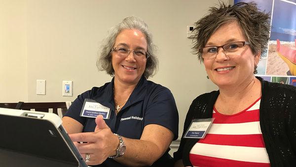 Pleasant Holidays' Maria Landrau-Mackey (left) demonstrates the tour company's new Hotel Recommendation tool to AAA Reading-Berks travel consultant Amy Kepner.