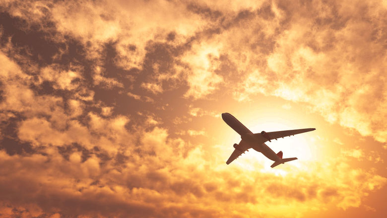 Airplane in the sky sunset [Credit: StudioByTheSea/Shutterstock.com]