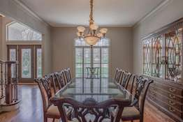 Formal Dining Room with Crown Molding and Large Sunburst Window