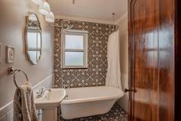 Delightful Main Floor Bath that has been restored with tile flooring, tile surround, and a 1914 claw foot tub!