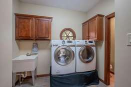 Main Floor Laundry Room with a utility sink, coat closet, and an additional Powder Room!