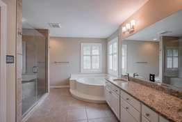 Corner Tub and Oversized Dual Sink Vanity Topped with Granite