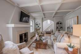 Living Room featuring a coffered ceiling, and peaked archways!