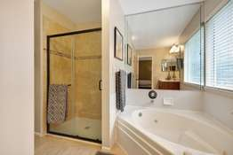 Corner Jetted Tub, Separate Shower with a Tile Surround