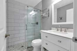 Recently Remodeled Master Bath with Quartz Topped Vanity, Tile Surround Shower, and Ceramic Tile Flooring