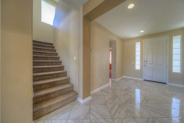 Foyer with access to Downstairs bedroom/bath, garage, and stairs