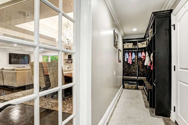 MUD ROOM WITH CUSTOM BUILT-IN CABINETRY AND A FRENCH DOOR TO THE KITCHEN