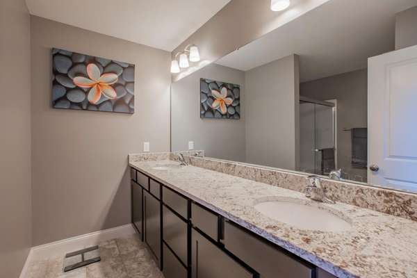 Master Bathroom includes a comfort height dual sink vanity, semi-frameless glass shower with a seat, and a linen closet