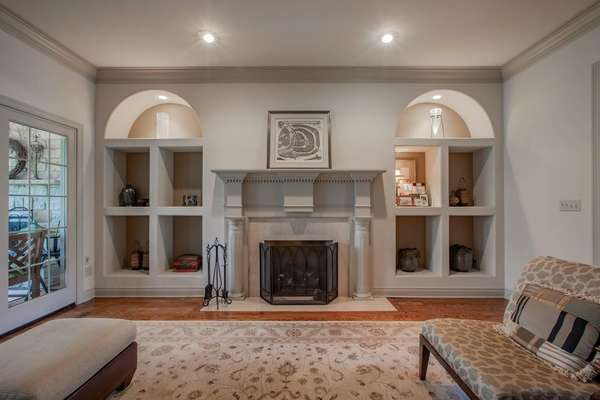 Gas Fireplace Flanked by 2 Art Nooks with Lighting