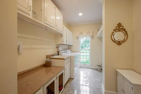 Main Floor Laundry/Mudroom with granite tiled flooring, and custom cabinetry - including a built-in dog kennel!