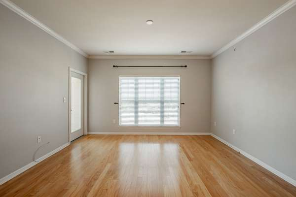 Living Room with Gleaming Hardwood Floors and Access to the Private Balcony