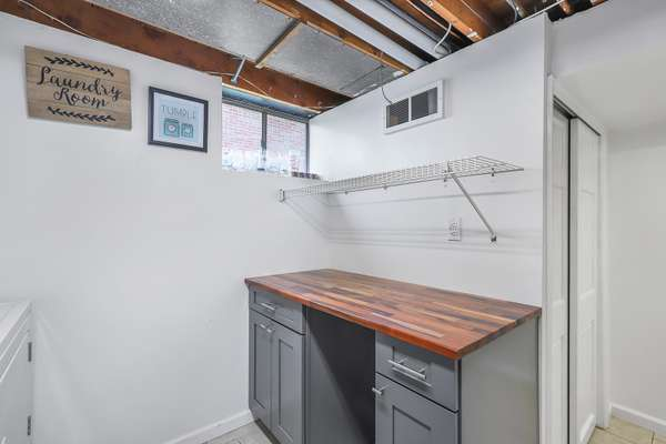Laundry Room Offers Cabinetry and a Utility Sink